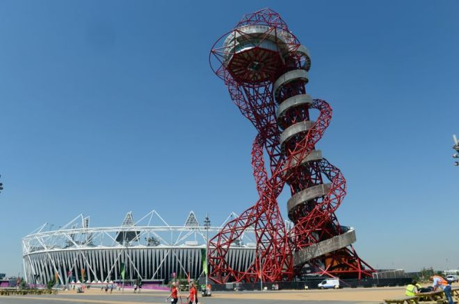 The ArcelorMittal Orbit sculpture (R) by British artist Anish Kapoor (R) is pictured in front of the Olympic Stadium at the Olympic park in London on July 24, 2012, three days ahead of the opening of the London 2012 Olympic Games. AFP PHOTO / ADEK BERRY