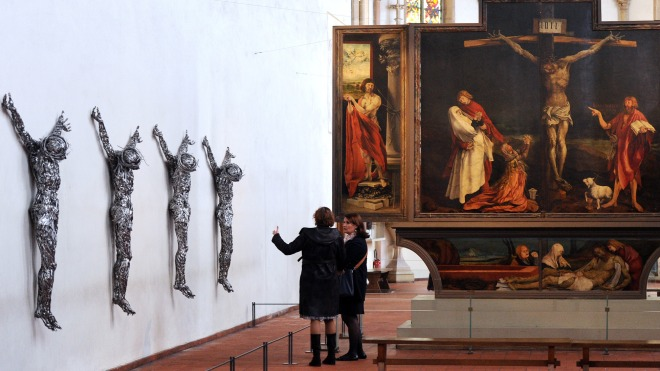 """Visitors look at contemporary sculptures untitled """"Decor"""" by Algerian artist Adel Abdessemed on April 24, 2012 at the chapel of the Unterlinden museum in the northeastern French city of Colmar, exhibited besides the """"Isenheim Altarpiece"""" (aka """"retable d'Issenheim"""" in French) by German Renaissance painter Matthias Grunewald, as part of the 500-year anniversary of this famed Renaissance religious work. Abdessemed borrowed the image of Christ crucified from Mattias Grünewald to create four crucified Christ, laced with industrial grade razor wire. His work will be shown for the first time in Europe from April 27 to September 16, 2012 in Colmar. AFP PHOTO / PATRICK HERTZOG"""
